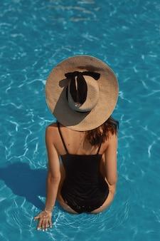 Młoda piękna kobieta z seksownymi dużymi piersiami i szczupłą talią w czarnym stroju kąpielowym pozuje na basenie na świeżym powietrzu w letni dzień.