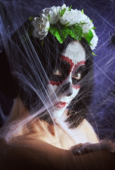 Młoda piękna kobieta z tradycyjną meksykańską maską śmierci. calavera catrina. makijaż czaszki cukru. kobieta ubrana w wieniec róż