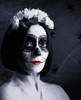 Młoda piękna kobieta z tradycyjną meksykańską maską śmierci. calavera catrina. makijaż czaszki cukru