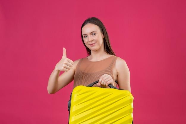 Młoda piękna kobieta z walizką podróżną patrząc na kamery z radosną buźką uśmiechnięty pokazując kciuki stojąc na różowym tle