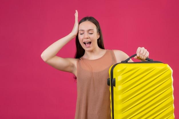 Młoda piękna kobieta z walizką podróżną stojąc z ręką na głowie za błąd pamięta błąd na różowym tle