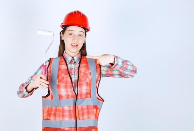 Młoda piękna kobieta z wałkiem do malowania naprawy ścian.