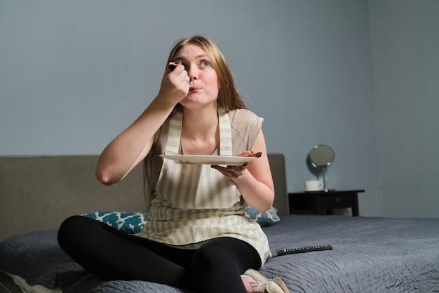 Młoda piękna kobieta z zainteresowaniem oglądanie telewizji i jedzenie, kobieta siedzi na łóżku ze świeżą, domową żywnością, z pilotem, relaks w domu