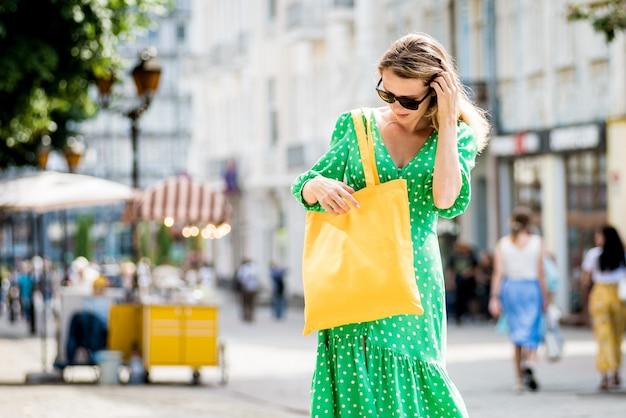 Młoda piękna kobieta z żółtą lnianą eko torbą na tle miasta