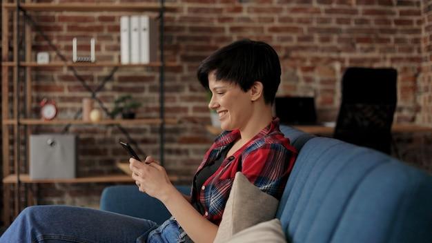 Młoda piękna kobieta za pomocą aplikacji na telefon komórkowy, wiadomości tekstowe, patrząc na smartfona i uśmiechając się.