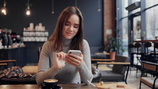 Młoda piękna kobieta za pomocą aplikacji na telefon komórkowy, wiadomości tekstowe