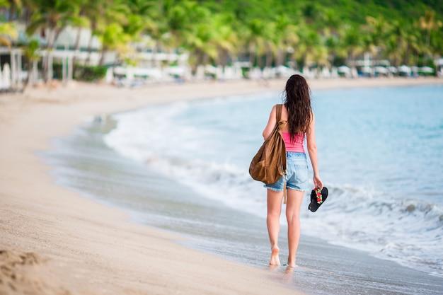 Młoda piękna kobieta zabawy na tropikalnym wybrzeżu. szczęśliwa dziewczyna spaceru na białym piasku tropikalnej plaży