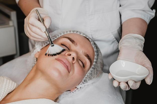 Młoda piękna kobieta zaczyna zabieg na skórę twarzy w centrum odnowy biologicznej