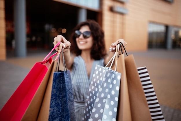 Młoda piękna kobieta zakupoholiczka wychodzi z centrum handlowego z paczką toreb z zakupami.