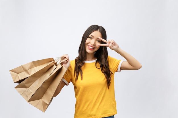 Młoda piękna kobieta zakupy z torby na zakupy pokazuje dwa palce