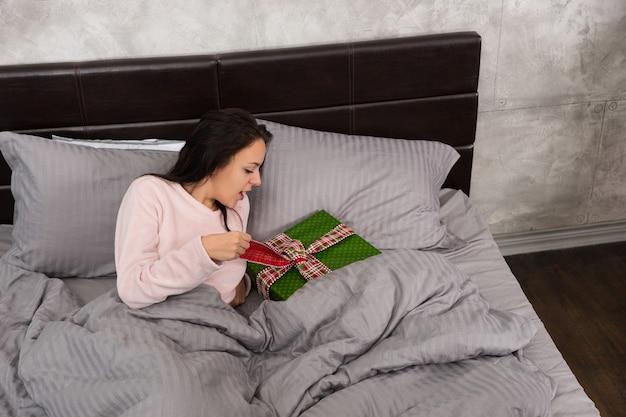 Młoda piękna kobieta zaskoczona prezentem świątecznym leżącym na poduszce w sypialni w stylu loft
