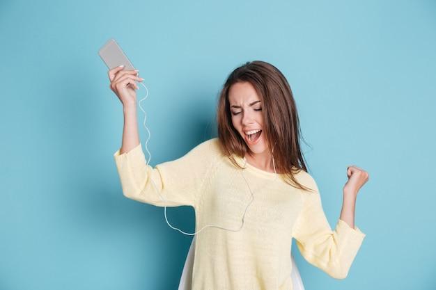 Młoda piękna kobieta ze słuchawkami tańczącymi na białym tle na niebieskim tle