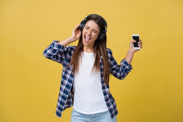 Młoda piękna kobieta ze słuchawkami taniec i śpiew na białym tle na żółtym tle.