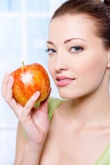Młoda piękna kobieta zmysłowość z jabłkiem - w pomieszczeniu