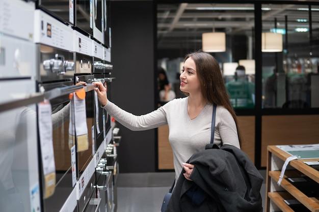Młoda piękna kobieta znajduje się piekarnik lub kuchenka gazowa w sklepie supermarketu.
