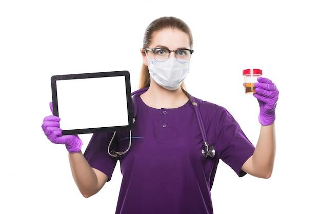 Młoda piękna kobiety lekarki mienia próbka moczu i pastylka w jej rękach w medycznej masce i bezpłodnych rękawiczkach na bielu
