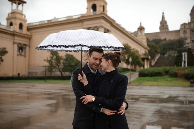 Młoda piękna kochająca latynoska para chodzi pod parasolem podczas deszczu w placu hiszpania. para pozuje na tle narodowego muzeum sztuki katalonii.