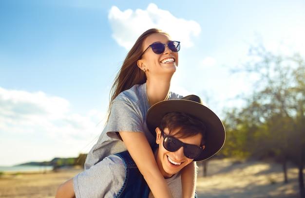 Młoda piękna kochająca para w modnym stylu mody pozuje na słonecznej plaży w koszulowej czapce bejsbolowej i okularach przeciwsłonecznych, szczęśliwie uśmiechając się i śmiejąc. portret z bliska na zewnątrz