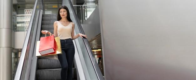 Młoda piękna koreańska kobieta stoi na schodach ruchomych w centrum handlowym. w rękach trzyma torby z zakupami. spadać. miejsce na tekst