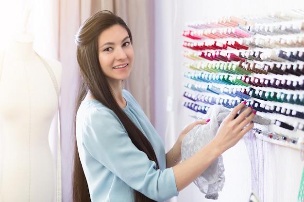 Młoda piękna krawcowa, patrząc na nici do tkanin w swoim miejscu pracy.