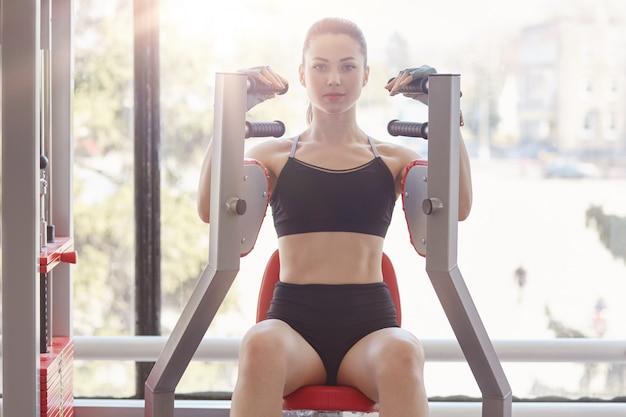 Młoda piękna kulturystka pracująca na stacji fitness w siłowni, trenująca biceps i triceps, ćwicząca na górnej części ciała, chce rozwinąć definicję mięśni.