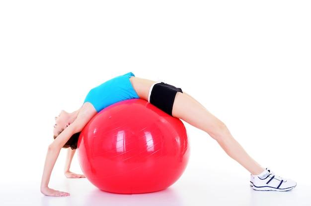 Młoda piękna ładna dziewczyna robi ćwiczenia fizyczne z fitball