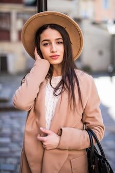 Młoda piękna ładna kobieta z długimi włosami, spacery wzdłuż ulicy, ubrana w dorywczo ubrania jesienią