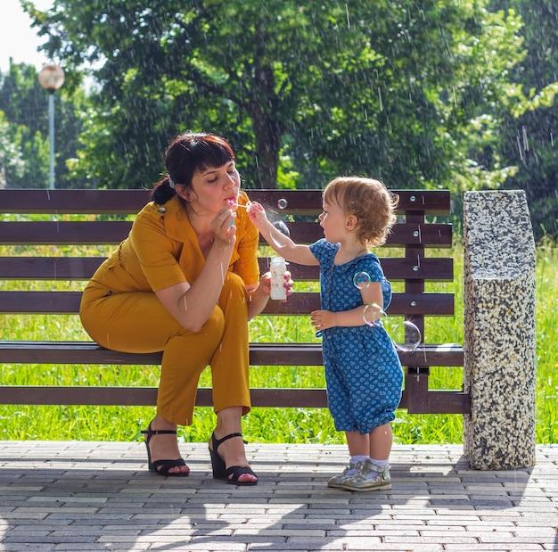 Młoda piękna mama i jej córeczka siedzą szczęśliwie na ławce w parku i dmuchają bańki mydlane na tle letniego deszczu w słoneczny dzień