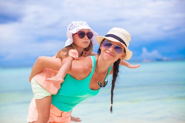 Młoda piękna mama i jej urocza córeczka bawią się na tropikalnej plaży