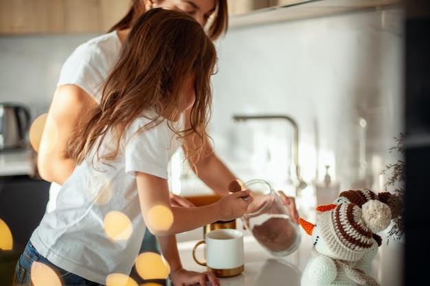 Młoda piękna mama i płacząca córka przygotowują kakao w stylowej domowej kuchni