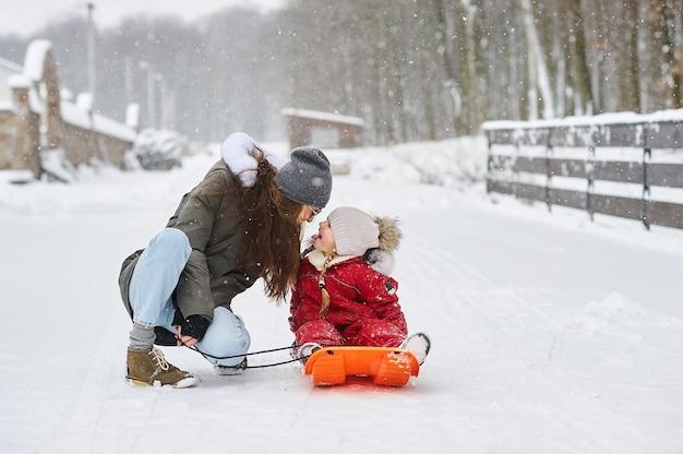 Młoda piękna mama sanki swoje dziecko