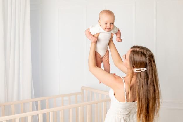 Młoda piękna mama trzyma w ramionach swoją sześciomiesięczną córkę, unosząc ją w pokoju dziecinnym stojącym przy łóżeczku