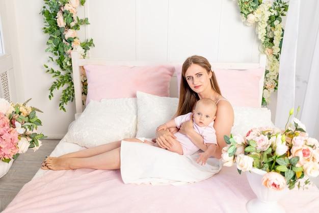 Młoda piękna mama z sześciomiesięczną córką na rękach siedzi na białym łóżku w kwiatach i przytula ją, miejsce na tekst