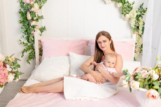 Młoda piękna mama z sześciomiesięczną córką na rękach siedzi na białym łóżku w kwiatach i przytula ją