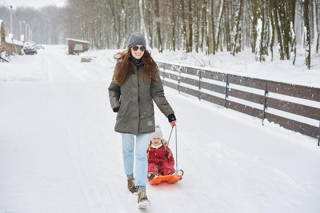 Młoda piękna mama zaprzęga swoje dziecko na sankach. rodzinne wakacje i koncepcja szczęśliwego czasu