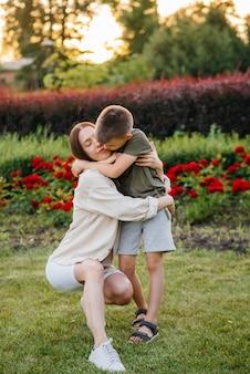 Młoda piękna matka całuje i przytula swojego synka podczas zachodu słońca w parku. szczęśliwa rodzina spacer po parku.