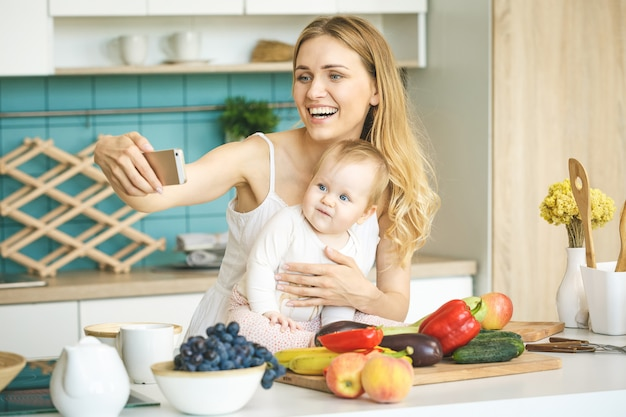 Młoda piękna matka gotuje i bawi się z córeczką w nowoczesnej kuchni. robienie selfie w aparacie.