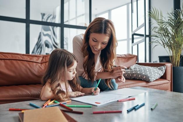 Młoda piękna matka i jej córeczka rysowanie w szkicowniku, siedząc na kanapie w domu