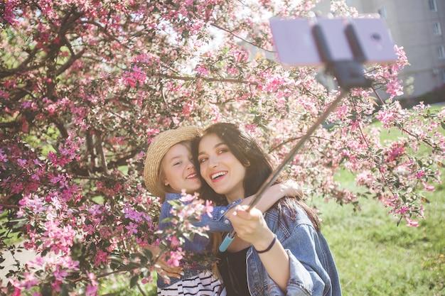 Młoda piękna matka i jej mała córka robi selfie przy telefonem komórkowym.