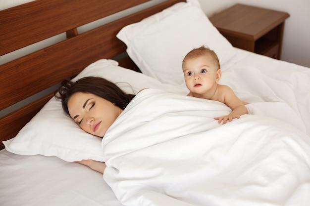 Młoda piękna matka i jej noworodka leżącego śpiącego w łóżku wcześnie rano.