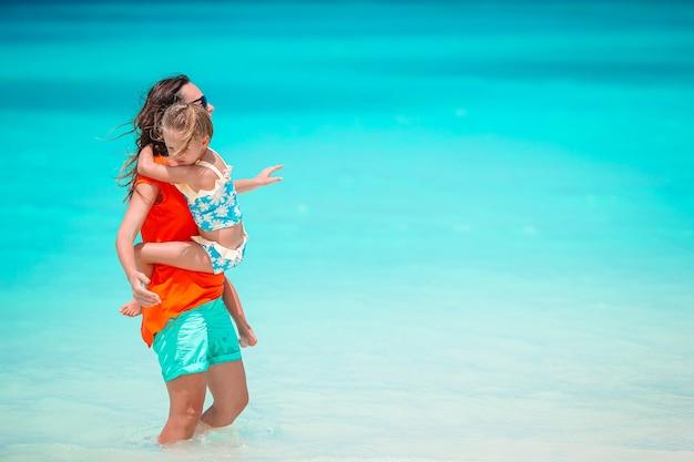 Młoda piękna matka i jej urocza córeczka bawią się na tropikalnej plaży