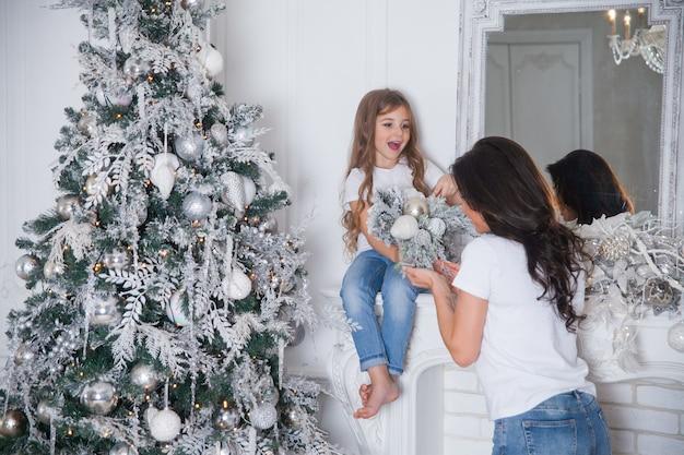 Młoda piękna matka i mała śliczna córeczka w białych koszulkach i dżinsach, zabawy i przytulanie pod udekorowaną choinką. świąteczne klasyczne wnętrze domu z lustrem.