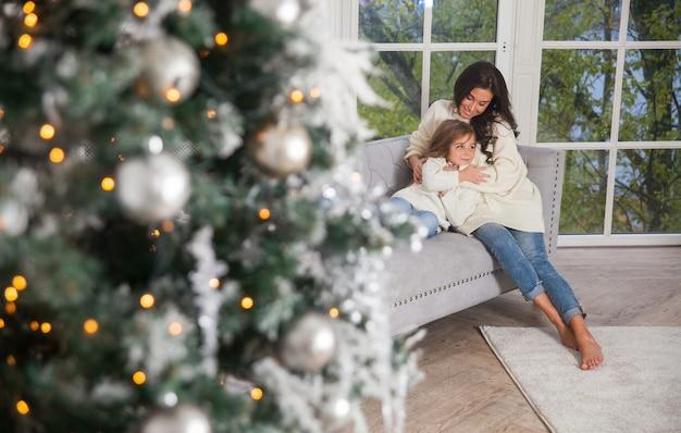Młoda piękna matka i mała śliczna córeczka w białych wygodnych swetrach przytulanie na kanapie obok okna i udekorowana choinka. świąteczne klasyczne wnętrze domu.