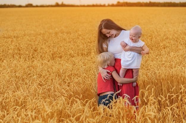 Młoda piękna matka spaceruje po polu z dwójką dzieci. weekendowe wyjazdy. szczęśliwa rodzina na zewnątrz.