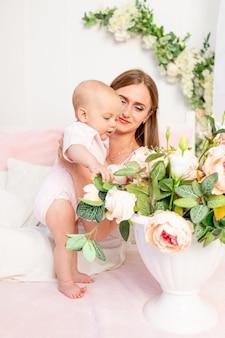 Młoda piękna matka trzyma córkę, dziewczynkę w wieku 6 miesięcy na białym łóżku i patrzy na kwiaty, miejsce na tekst