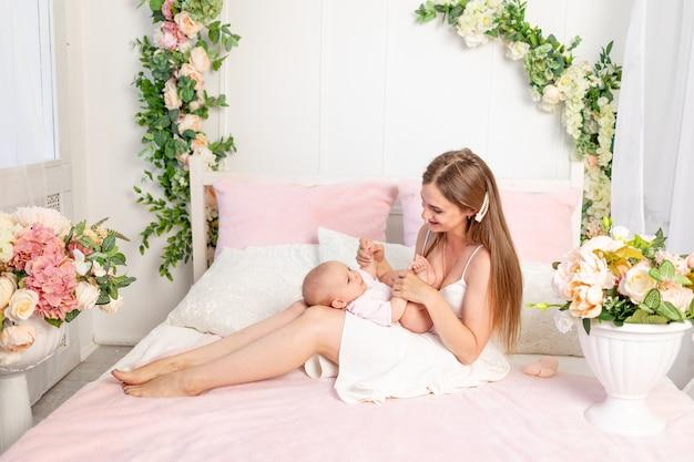 Młoda piękna matka trzyma córkę na białym łóżku, grając i całując ją