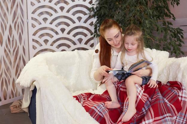 Młoda piękna matka z córeczką czyta książkę, siedząc na kanapie.