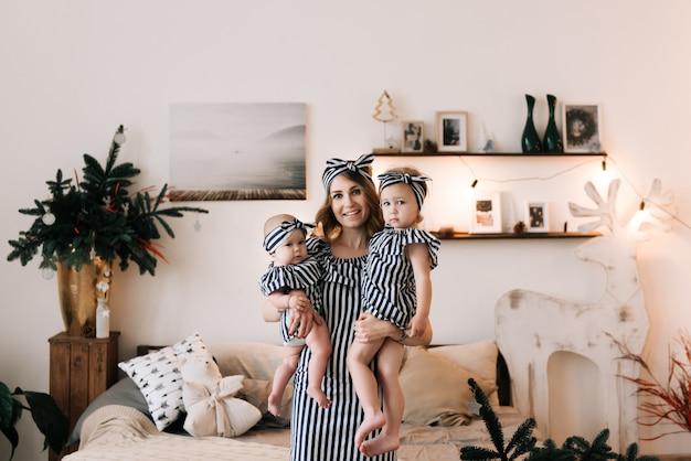 Młoda piękna matka z dwiema córkami w boże narodzenie wystroju studiu. wesołych świąt i nowego roku koncepcja