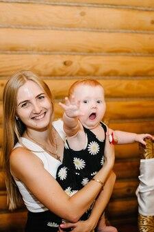 Młoda piękna matka z małą dziewczynką na rękach siedzi na drewnianej ścianie. niemowlę. szczęśliwa rodzina.