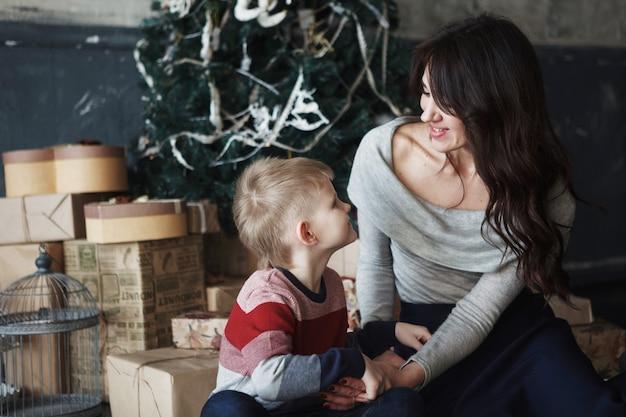 Młoda piękna matka z synem w pobliżu choinki